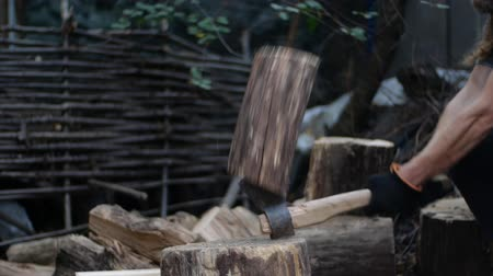 fejsze : Man chops wood outdoors in slow motion. Mans hands working with ax. A man woodcutter chops tree trunks with an ax for firewood. Stock mozgókép