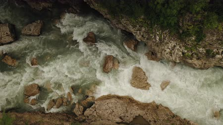 zuhatag : Aerial drone top view of a deep Hadzhokh Gorge and fast white stream of river Belaya . Beautiful view of mountain river on summer sunny day in mountains of Adygea, Russia.
