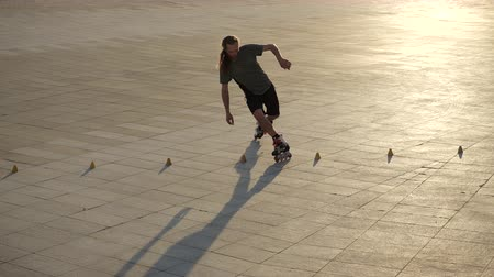inline : Young long-haired man roller skater is dancing between cones in a nice evening in a city park. Freestyle slalom Roller skating between cones in slow motion.