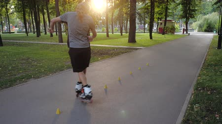 inline skating : Young long-haired bearded man roller skater is dancing between cones in a nice evening in a city park. Freestyle slalom Roller skating between cones in slow motion.