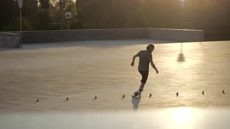 inline skating : Young long-haired man roller skater is dancing between cones in the evening in a city park at sunset. Freestyle slalom Roller skating between cones. Stock Footage