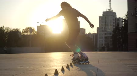 inline skating : Young long-haired man is professionally skating between cones on a nice evening sunset in a city park. Freestyle slalom Roller skating between cones. Stock Footage