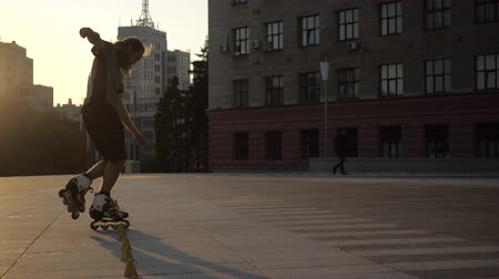roller blading : Young long-haired man is professionally skating between cones on a nice evening sunset in a city park. Freestyle slalom Roller skating between cones. Stock Footage