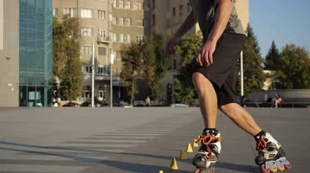 roller blading : Young long-haired man roller skater is dancing between cones in the evening in a city square at sunset. Freestyle slalom Roller skating between cones in slow motion.
