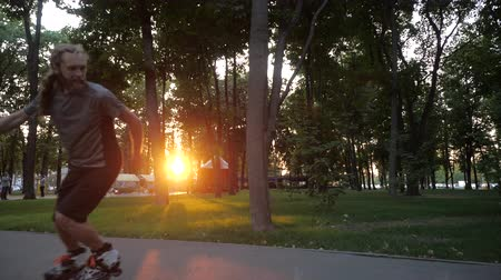inline : Young long-haired bearded man roller skater is dancing in a nice evening in a city park showing thumb up. Freestyle Roller skating at sunset. Stock Footage