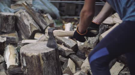 hatchet : Man chops wood outdoors in slow motion. Mans hands working with ax. A man woodcutter chops tree trunks with an ax for firewood. Stock Footage