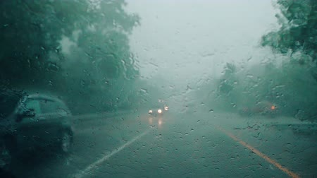 Car wipers cannot remove heavy rain from a car windshield during storm, difficult driving conditions.