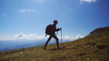 достигать : Young woman with backpack and trekking poles walks uphill towards the summit against blue sky. Slow motion. Lady is hiking in beautiful Caucasian mountains.
