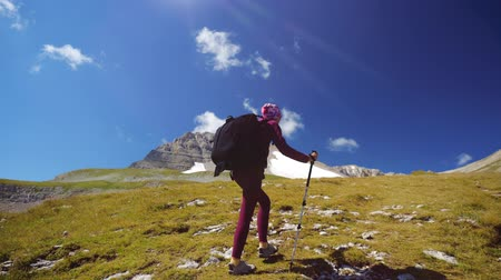 альпинист : Tracking shot of a Young woman with backpack and trekking poles walks uphill towards the summit. Slow motion. Lady is hiking in beautiful Caucasian mountains. Стоковые видеозаписи