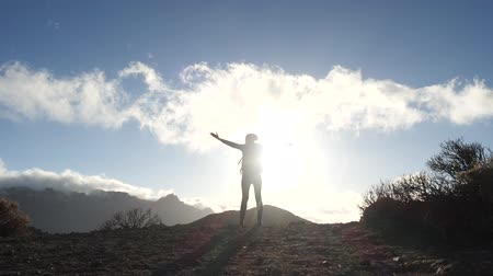альпинист : Silhouette of a standing young woman with backpack on the background of blue sky and clouds. Lady arms outstretched in beautiful mountains on Canary Islands.