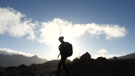 альпинист : Silhouette of a young woman hiker with backpack walking uphill towards the summit against blue sky and clouds at sunset. Slow motion. Lady is hiking in beautiful mountains on Canary Islands. Стоковые видеозаписи
