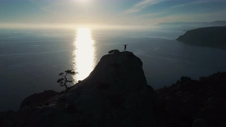 альпинист : Aerial silhouette of young woman standing on the top of a mountain against the sea at sunrise. Happy young woman on top of a mountain in Crimea with arms outstretched. Lady mountaineer on the summit