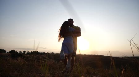 hayran olmak : A love story of a young charming couple in rural landscape at sunset. Silhouette of bearded young man holding and twirling his girlfriend at breathtaking golden sunset. Stok Video
