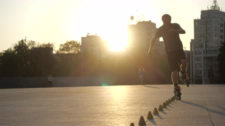 inline skating : Young long-haired man roller skater is dancing between cones in the evening in a city square at sunset. Freestyle slalom Roller skating between cones in slow motion.