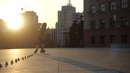 inline : Young long-haired man roller skater is dancing between cones in the evening in a city square at sunset. Freestyle slalom Roller skating between cones in slow motion.