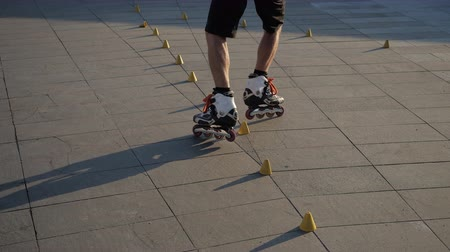 inline : Close-up legs of a young man is professionally skating between cones on a nice evening sunset in a city park. Freestyle slalom Roller skating between cones.