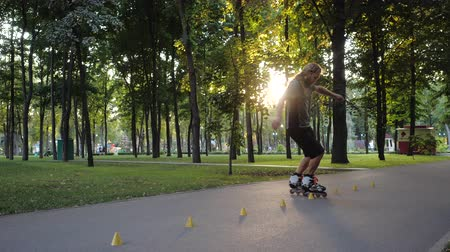 inline : Young long-haired bearded man roller skater is dancing between cones in a nice evening in a city park. Freestyle slalom Roller skating between cones in slow motion.
