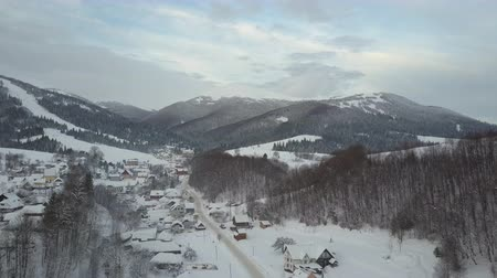 surroundings : Flight over a village in Carpathian mountains and a ski resort next to it. Birds eye view of snow-covered houses in mountains. Rural landscape in winter. Carpathian village in the snow from a height. Stock Footage