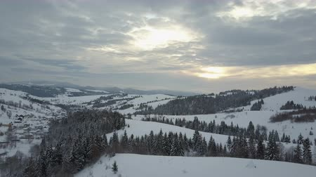 surroundings : Flight over a village in Carpathian mountains at sunrise. Birds eye view of snow-covered houses in mountains. Rural landscape in winter. Carpathian village in the snow from a height.