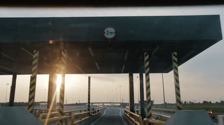 virgem : POV driving along a wide empty morning road early in the morning during sunrise.. Point of view driving, view from inside the car on on the autobahn in Poland. Entry or exit to a toll road section.