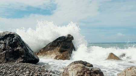 krím : Panoramic shot from the sky to sea waves crashing on stones and spraying in Slow motion. Beautiful Beach in Crimea with stones and sand, Stock mozgókép