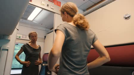 přihrádka : A young woman looks to a peephole modern comfortable train compartment. Then she unlocks and opens a mirror door with metal handle and exits. A train passenger unlocks a door.