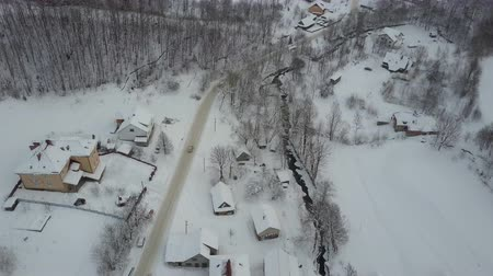 faház : Aerial view of cars moving on winter road in Carpathian village. Birds eye view of snow-covered houses. Rural landscape in winter.