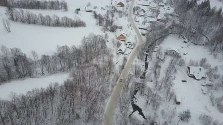 surroundings : Aerial view of a car moving on winter road in Carpathian village. Birds eye view of snow-covered houses. Rural landscape in winter.
