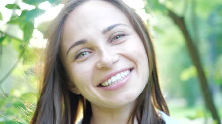 womanhood : Close up portrait of Young beautiful brunette girl with clean, natural skin smiling and laughs laughing showing her white teeth. Pretty Woman with hair blowing in wind looking at camera.