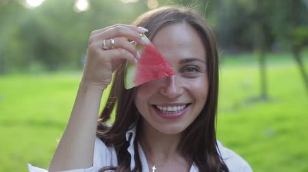 melão : Closeup portrait of girl smelling aroma and eating a red healthy juicy watermelon, fooling and laughing on a green background. Fruit - the benefits of green foods and natural healthy nutrition.