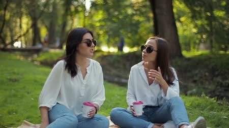 ele geçirmek : Two stylish happy smiling girls in white shirts are sitting in the park on a soft background of green foliage. Girlfriends have fun, discuss important issues, drink coffee in paper cups. Stok Video