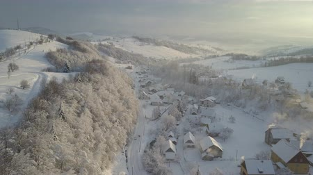 surroundings : Flight over a village in Carpathian mountains in winter at sunrise. Aerial view of snow-covered houses in mountains. Rural landscape in winter. Mountain village in the snow from a height.