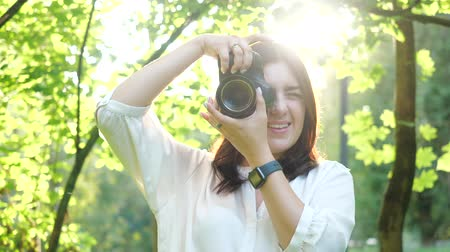 fotoğrafçı : Pretty smiling girl photographer in white shirt is making photos in a park on a soft background of green foliage. A woman photographs model looking at the camera through the rays of the sun at sunset. Stok Video