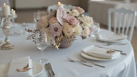 masa örtüsü : Close up of elegant, decorated table prepared for a luxury dinner. Dcorated table for a wedding dinner with burning candles Stok Video