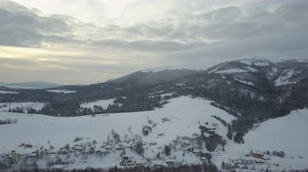 faház : Aerial panorama of a mountain village in winter at sunrise. Aerial view of snow-covered houses in mountains. Rural landscape in winter. Mountain village in the snow from a height. Stock mozgókép