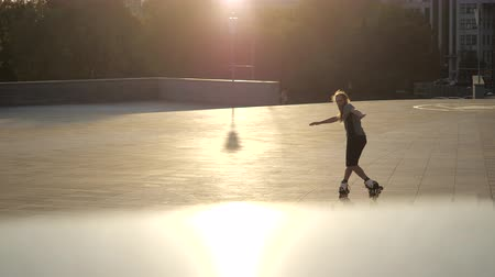 inline : Young long-haired bearded man roller skater is dancing between cones in the evening in a city park at sunset. Freestyle slalom Roller skating between cones.