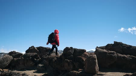 альпинист : Woman hiker with backpack walking towards the summit against blue sky and clouds. Slow motion. Lady is hiking in volcanic desert on Canary Islands.