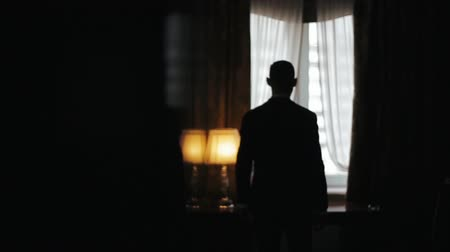 iluminado para trás : Silhouette of a Man wearing suit walking from a dark room towards a bright window in slow motion. Man stops, puts his hands on a table and looks pensive to the window.