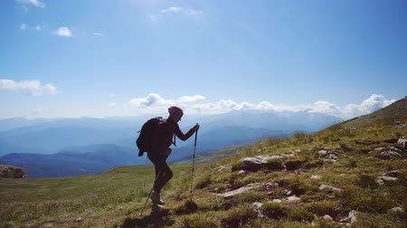альпинист : Young woman with backpack and trekking poles walks uphill towards the summit against blue sky. Slow motion. Lady is hiking in beautiful Caucasian mountains.