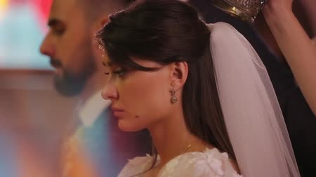 požehnat : Close-up side-view profile portrait of bride and groom in the Orthodox Church during the wedding ceremony.