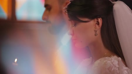 lasting : Close-up side-view profile portrait of bride and groom in the Orthodox Church during the wedding ceremony.