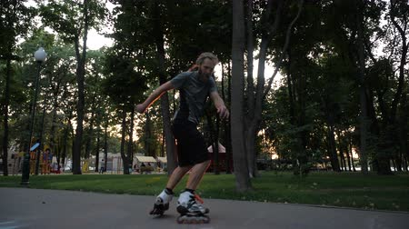 inline skating : Young long-haired bearded man roller skater is dancing in a nice evening in a city park. Freestyle Roller skating at sunset.