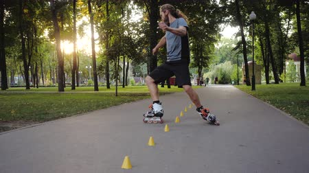 roller blading : Freestyle Roller skating at sunset. Young long-haired bearded man roller skater is dancing between cones in a nice evening in a city park showing thumb up.