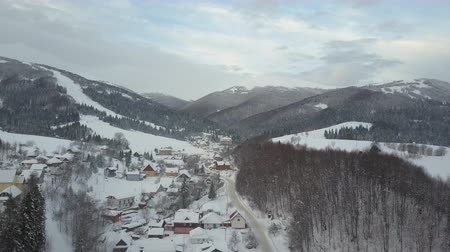 baita : Flight over a village in mountains at sunrise. Birds eye view of snow-covered houses in mountains. Rural landscape in winter. Carpathian village in the snow from a height.