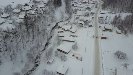 geada : Rural landscape in winter. Aerial view of a car moving on winter road in Carpathian village. Birds eye view of snow-covered houses.