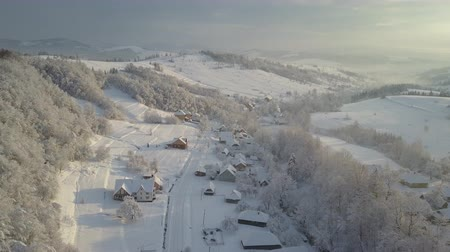 baita : Mountain village in the snow from a height. Flight over a village in Carpathian mountains in winter at sunrise. Aerial view of snow-covered houses in mountains. Rural landscape in winter.
