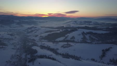 baita : Flight over Carpathian mountains in winter at sunrise. Rural landscape in winter from a height. Aerial view of a snow-covered mountain village.