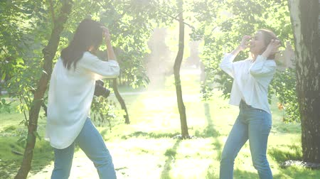 захват : Pretty girl professional photographer wearing white shirt is making photos of a happy smiling girl posing in a park on a soft background of green foliage and spraying water.