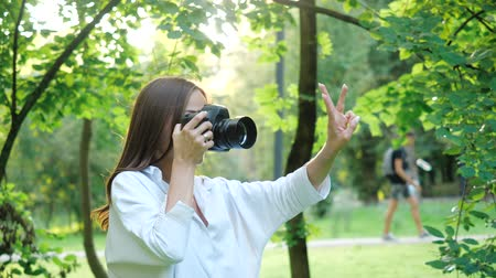 захват : Pretty girl photographer in white shirt is making photos and before taking a picture she shows on her fingers considers: one, two, three. A woman photographs model through the rays at sunset.