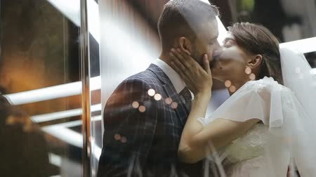 winda : The groom and the bride kiss in the elevator. Hugs are newlyweds, a girl pulls a guy by jacket to herself. Wedding love video. A man and a woman are smiling to each other and laughing.